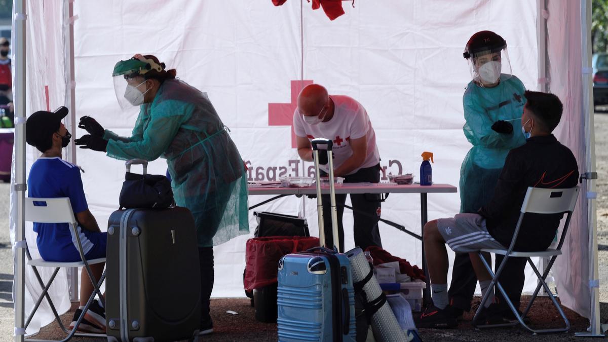 Varios trabajadores de Cruz Roja realizan una prueba PCR a un joven este jueves en Valladolid, momentos antes de subir al autobús que le lleva a un  campamento de verano. EFE/ Nacho Gallego