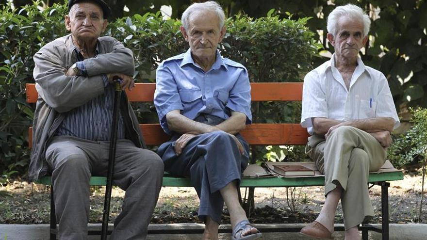 Imagen de archivo de tres ancianos en un banco.