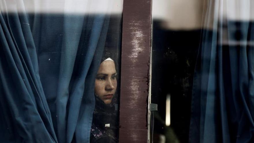 """Una refugiada espera para ser trasladada tras desembarcar del ferri """"Nissos Rodos"""", procedente de la isla de Lesbos, en el puerto del Pireo, cerca de Atenas, en Grecia."""