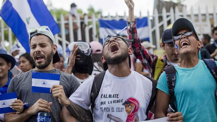 Tres jóvenes cantan el himno de Nicaragua frente a la Universidad Nacional Autónoma en Managua.