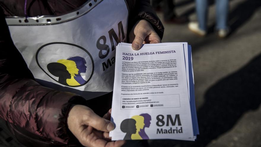 Una mujer muestra una hoja informativa sobre la huelga feminista en el mercado de Aluche.