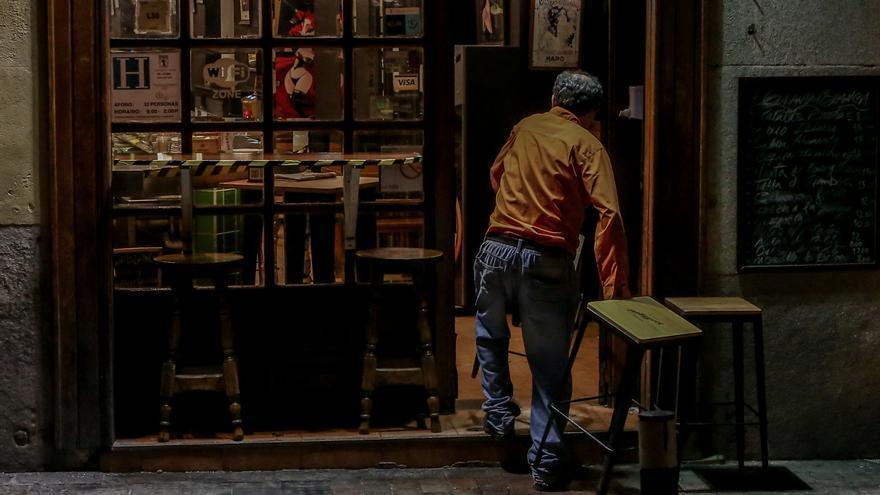 Un hombre cierra su restaurante el día en el que se adelanta el cierre de hostelería a las 22.00h, en Madrid