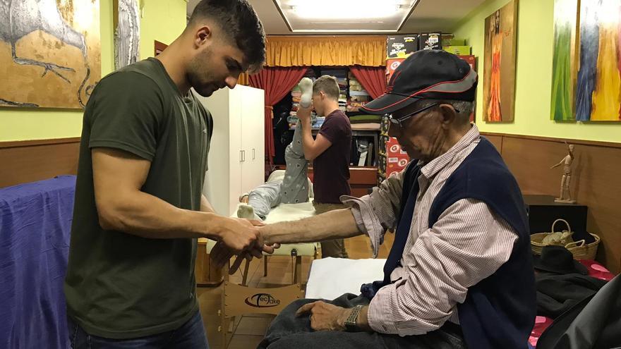 Marc Alati, un joven de 23 años que ha sido uno de los creadores de la asociación Mans Terapèutiques per Barcelona, atiende a una persona sin hogar en la Casa de Cádiz de Barcelona
