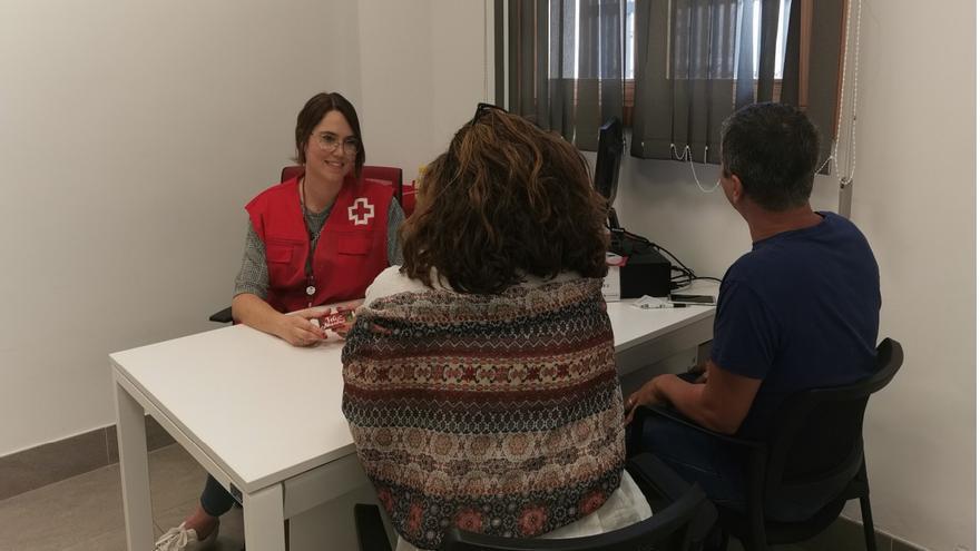 Una técnico de Cruz de Roja atiende a una de las familias beneficiarias del programa de atención social a menores.