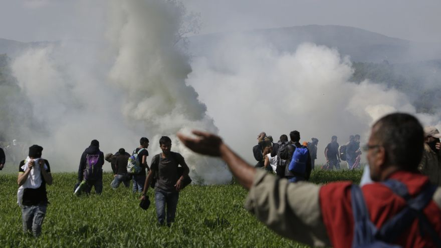Un grupo de personas huye del gas lacrimógeno que lanza la policía macedonia después de que un grupo de refugiados intentara romper la frontera en Idomeni, Grecia, 10 de abril de 2016. Foto:AP Photo/Amel Emric.