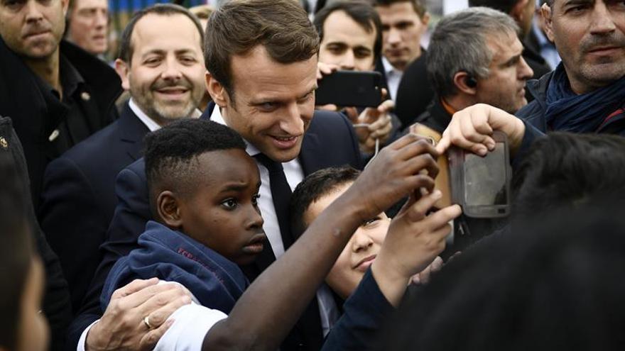 Macron, recibido entre vítores en la periferia parisina