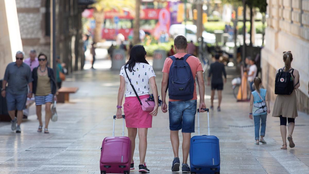 Imagen de archivo de varios turistas con sus equipajes por el centro de Málaga.