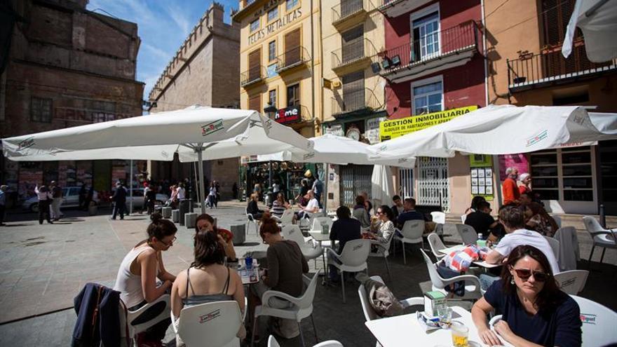 Varias personas disfrutan del buen tiempo en una terraza en la plaza del doctor Collado junto a La Lonja de Valencia