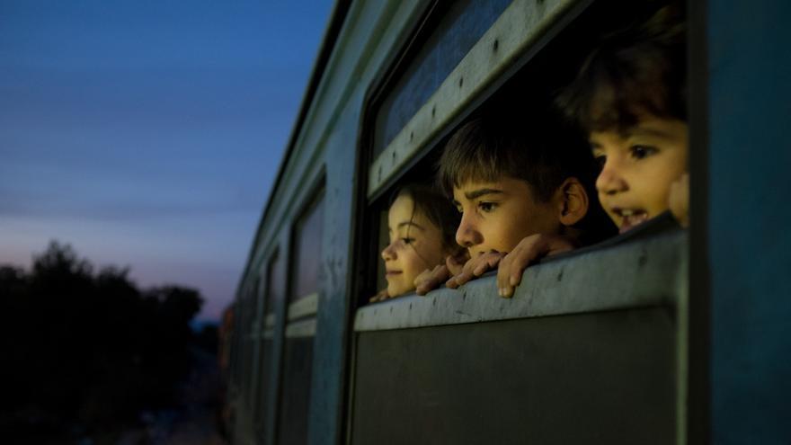 Tres niños refugiados miran por la ventana de un tren en la ex República Yugoslava de Macedonia, en octubre de 2015.