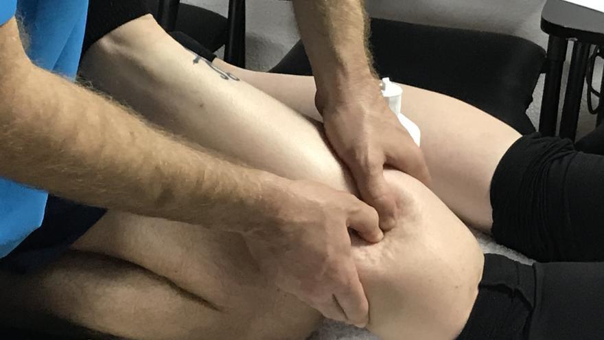 Una fisioterapeuta realiza un masaje de descarga a una corredora.