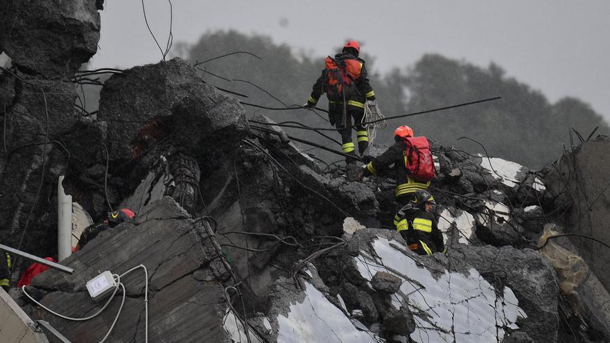 Miembros de los servicios de emergencia trabajan entre los escombros tras derrumbarse una sección del viaducto Morandi en Génova (Italia)