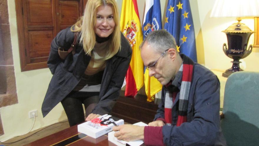 Carlos Felipe Martell firma un ejemplar este sábado a una lectora. Foto: LUZ RODRÍGUEZ.
