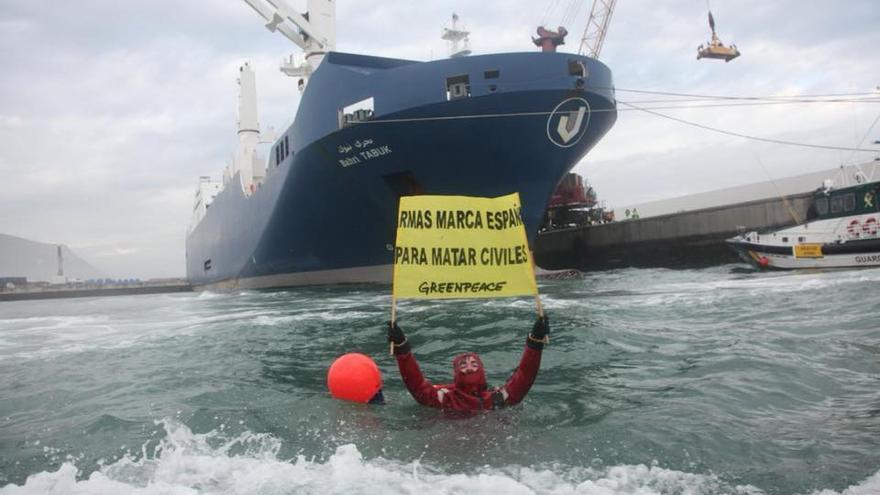 Un activista de Greenpace porta una pancarta ante el carguero saudí en señal de protesta.