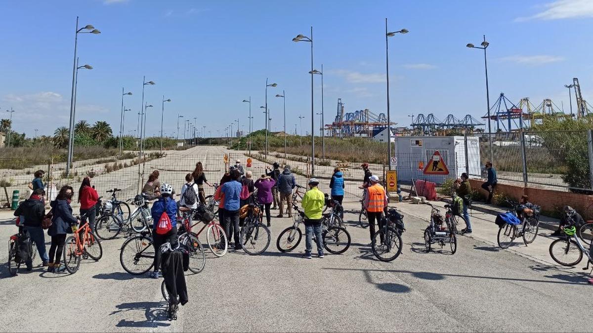 Los participantes frente al acceso de la ZAL, 23 años clausurado, con las grúas del puerto al fondo.