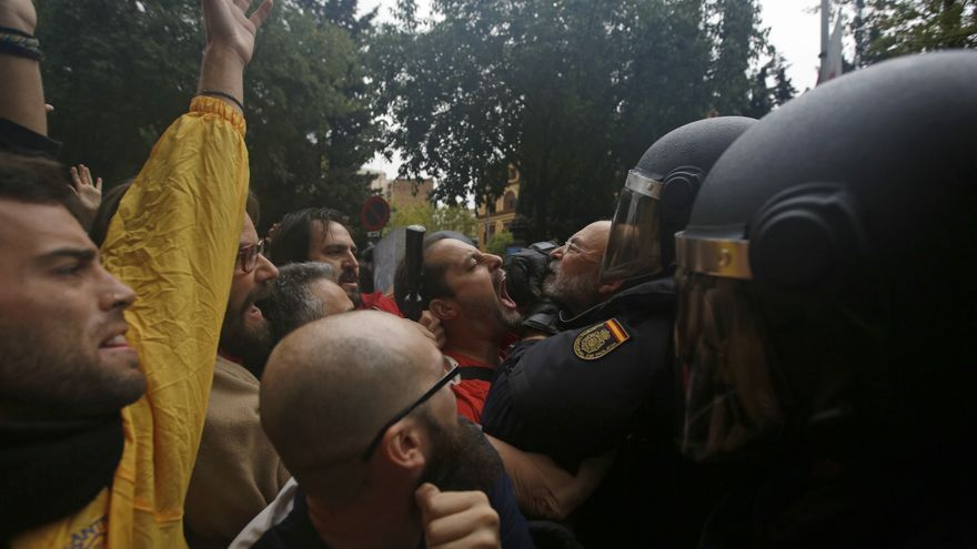 Spanish national police scuffle with people trying to reach a voting site at a school assigned to be a polling station by the Catalan government in Barcelona, Spain, Sunday, 1 Oct. 2017. Catalan pro-referendum supporters vowed Saturday to ignore a police ultimatum to leave the schools they are occupying to use in a vote seeking independence from Spain.