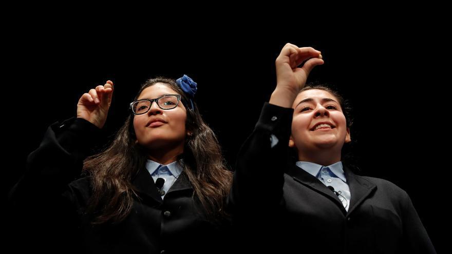 Las niñas Wendy Elizabeth Laborde (d) y Nicole Elizabeth Valenzuela muestran las bolas del número 750 agraciado con el tercer premio del Sorteo Extraordinario de la Lotería de Navidad que se celebra este domingo en el Teatro Real de Madrid.