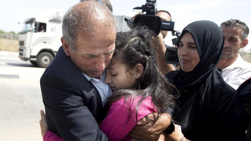 Dima al Wawi se abraza a su padre, ayer en el puesto de control de Jabara, cerca de Tulrkarem, en Cirsjordania (Majdi Mohammed / AP)