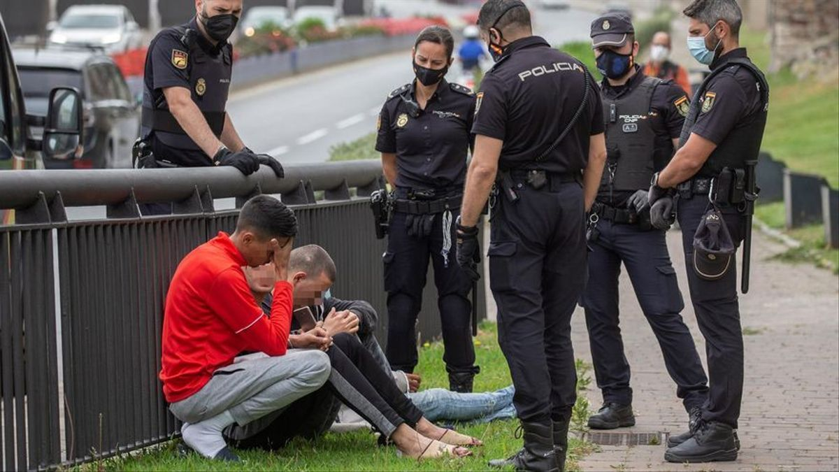 Imagen de archivo. Varios agentes de la Policía Nacional hablan con un grupo de inmigrantes en las calles de Ceuta este viernes. Brais Lorenzo/EFE