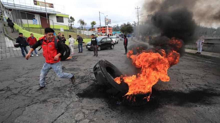 Un hombre quema llantas para bloquear una calle este jueves durante una jornada de protesta contra las medidas económicas del Gobierno del presidente de Ecuador Lenín Moreno, en Quito (Ecuador).