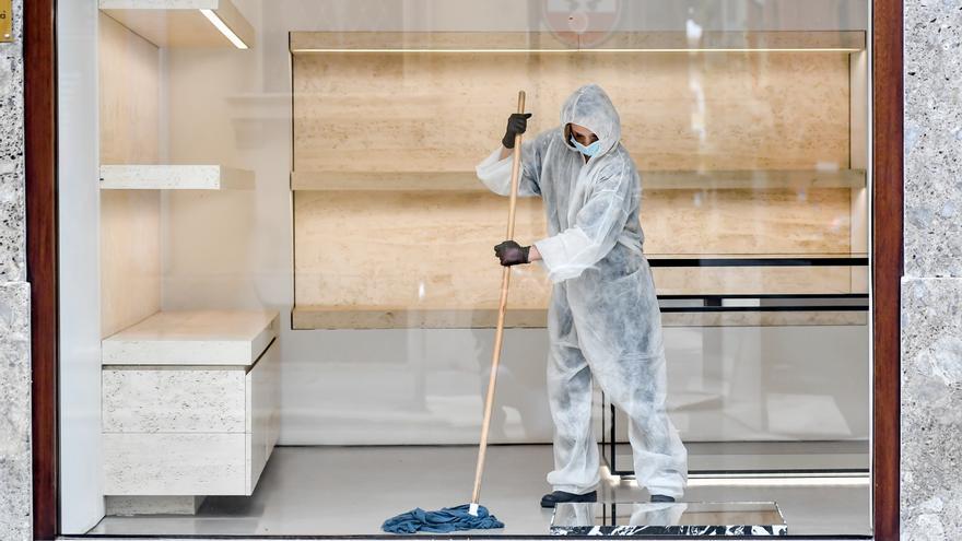 Un trabajador desinfecta una tienda en Milan (Italia) para evitar contagios de coronavirus.