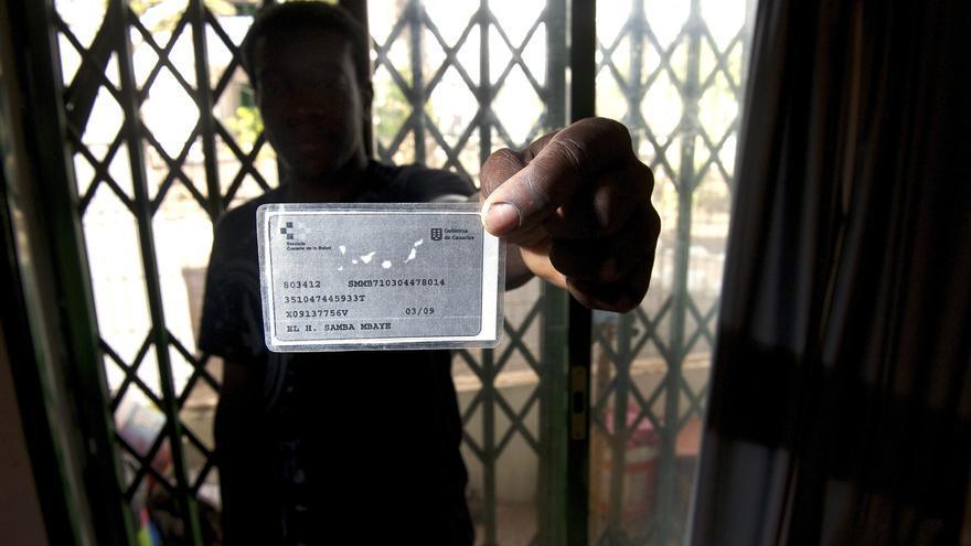 Un inmigrante en situación irregular muestra su tarjta sanitaria caducada. / Foto de archivo: Efe.
