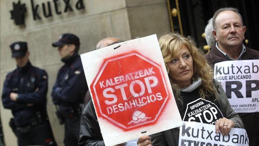 Una activista muestra un cartel de Stop Desahucios en una porotesta ante Kutxabank