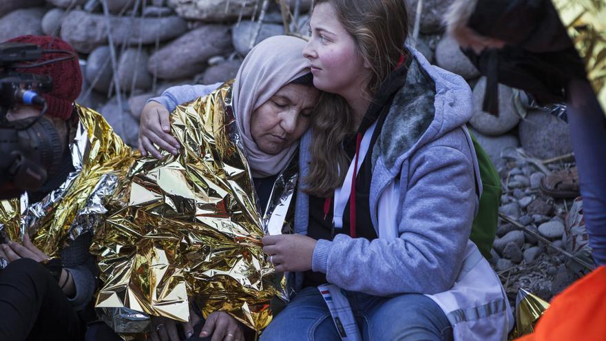 Un voluntaria trata de calentar a una mujer siria que acaba de desembarcar en Lesbos