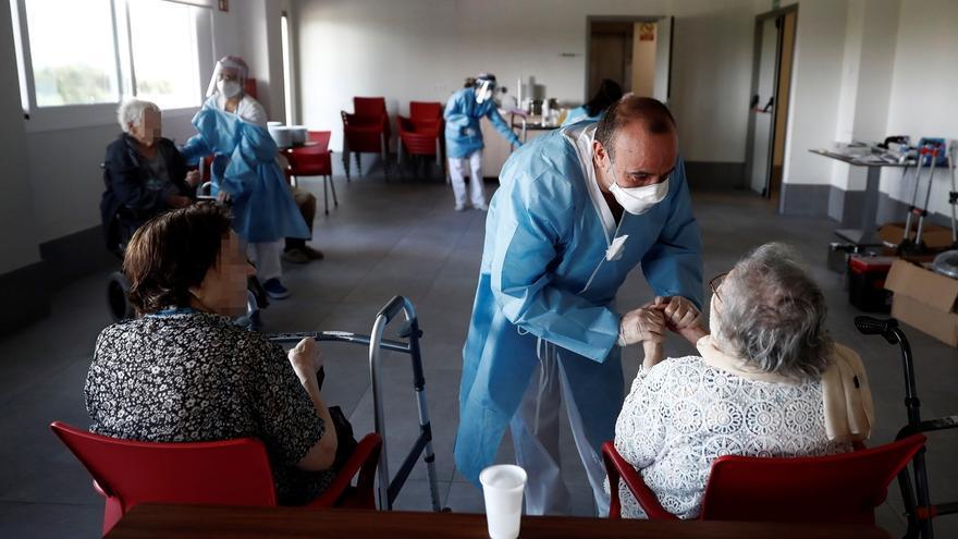 Un sanitario atiende a los ancianos alojados en una residencia.