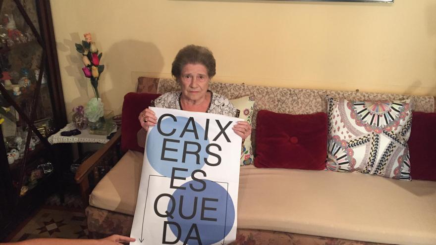Teresa Ramón en el salón de su casa muestra una pancarta de protesta