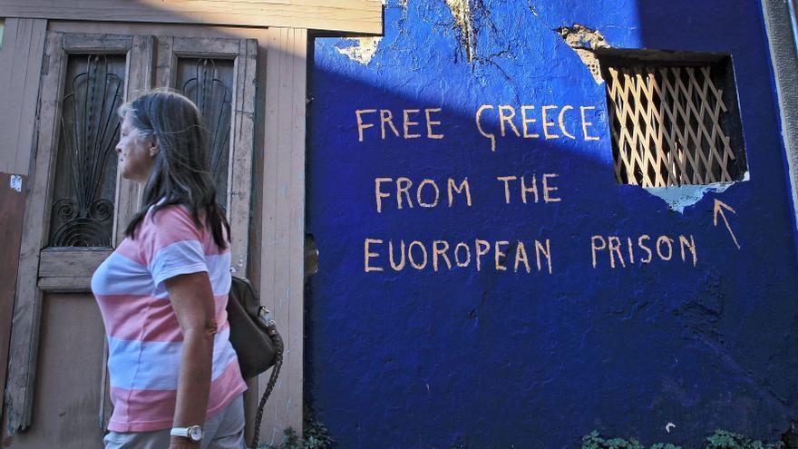 Una mujer pasa ante una pintada contra el euro en Atenas el 20 de junio. Foto: Simela Pantzartzi/EFE