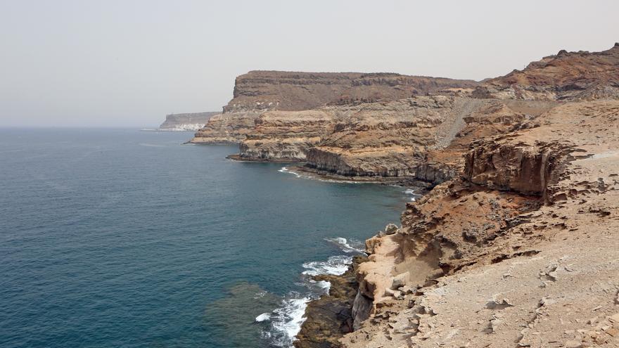 Acantilados en la costa de Mogán con el Puerto de Mogán al fondo