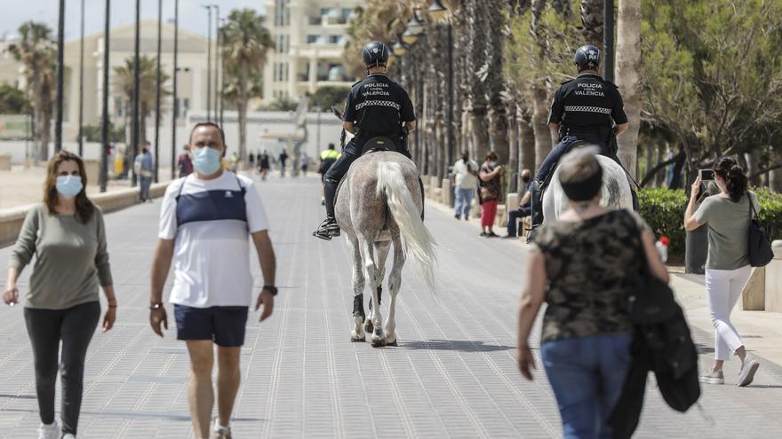 Archivo - Dos policías municipales patrullan a caballo por un paseo marítimo frente a una playa de València, a 26 de mayo de 2021