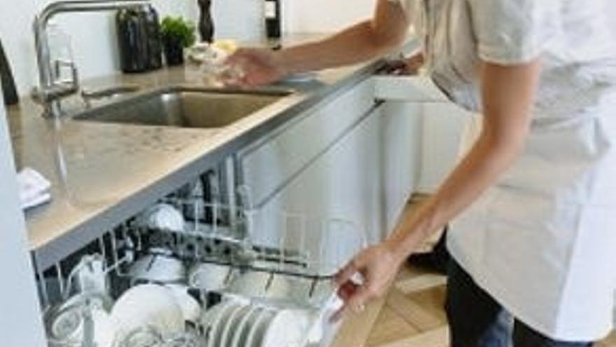 Una empleada de hogar trabaja en una cocina.