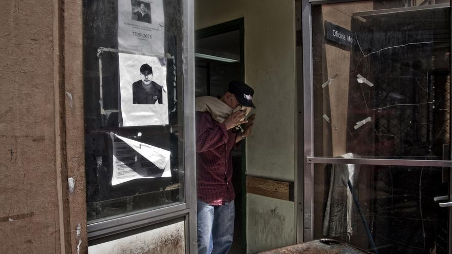 Un hombre llora en la puerta de la morgue del Hospital Rosales tras enterarse de que su hijo ha muerto. En las puertas de la morgue cuelgan carteles de gente desaparecida./Edu Ponces (RUIDO Photo)