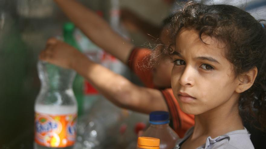 Los niños en Rafah, al sur de Gaza, recogen agua de uno de los grifos públicos/Oxfam