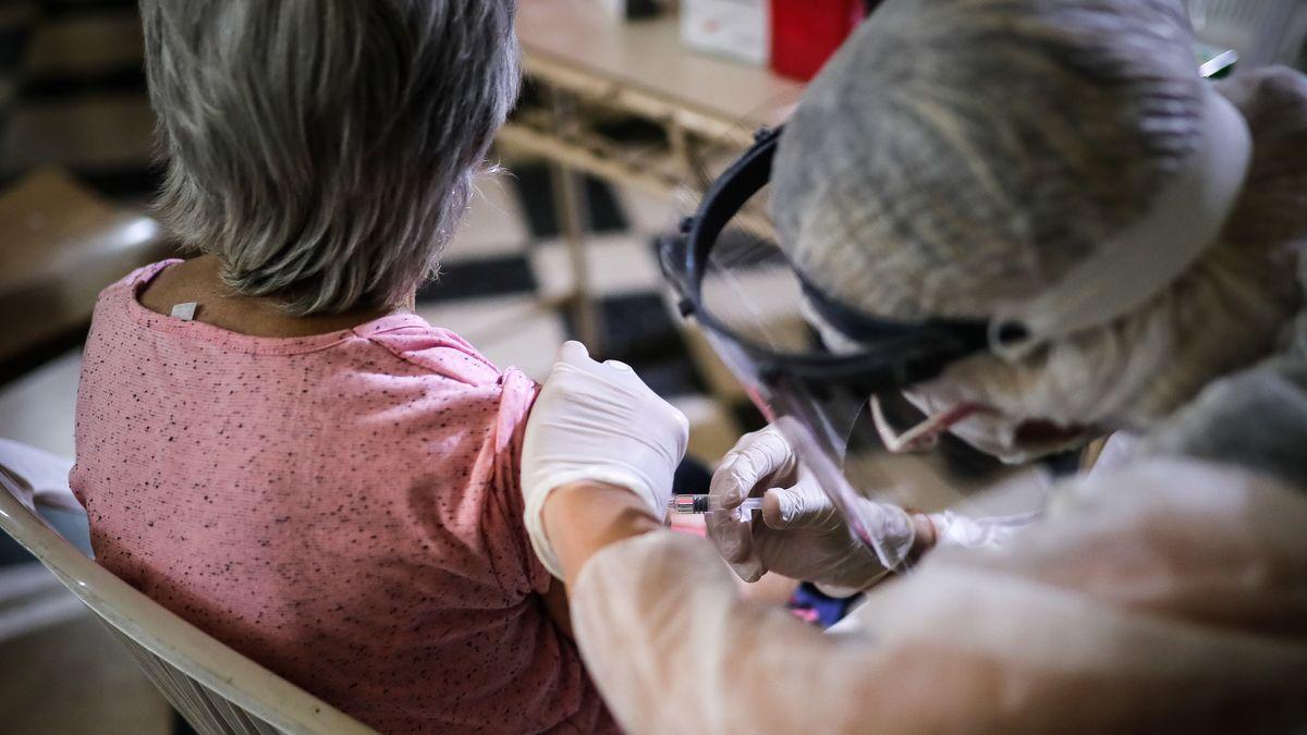 Imagen de archivo de un sanitario inyectando una vacuna.