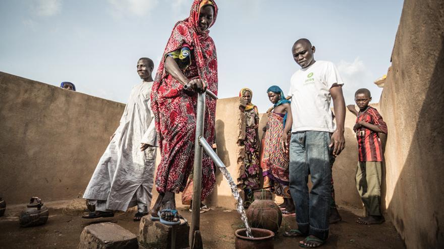 Akkoe Moussa, echando agua en un cántaro de cerámica junto a otras personas. FOTO: Pablo Tosco - Oxfam Intermón