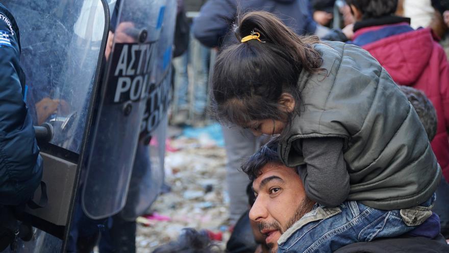 Un hombre y una niña esperan frente a la policía macedonia para poder cruzar la fronetra con Grecia. | Alfonso Font
