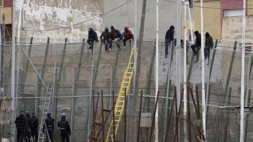 Una decena de inmigrantes encaramados en la valla de Melilla, en la zona del puesto fronterizo del Barrio Chino. / Efe.