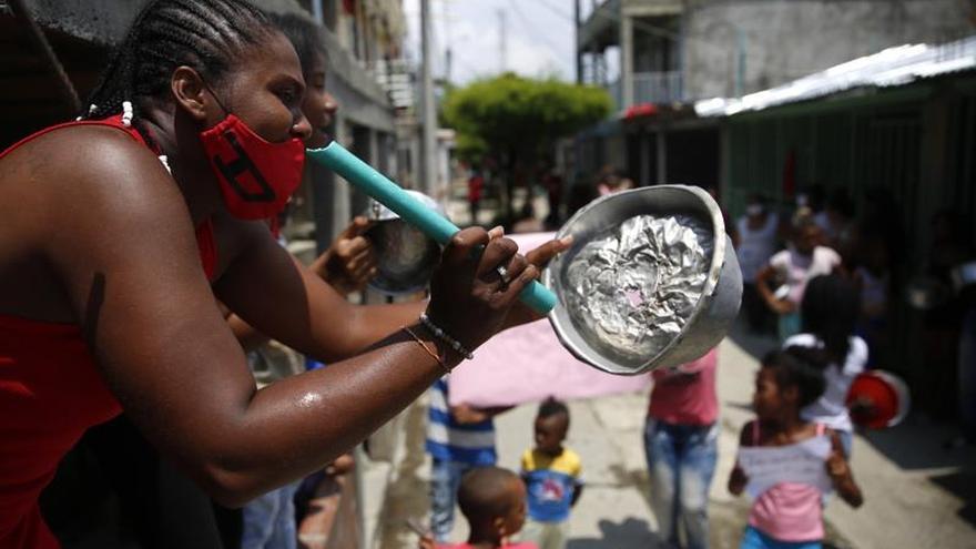 Una mujer golpea una cacerola en el barrio Tercer Milenio este jueves en Cali (Colombia). Decenas de personas salieron de sus casas haciendo sonar cacerolas para reclamar a la alcaldía por la falta de ayudas y alimentos en medio de la cuarentena por la emergencia del Covid-19.