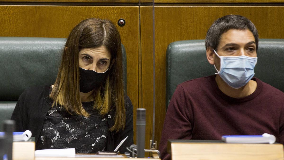 Los parlamentarios de la coalición Elkarrekin Podemos-IU Miren Gorrotxategi (i), y Jon Hernández, durante el pleno de investidura, que se celebra este jueves marcado por los protolocos anti-covid.