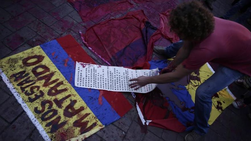 Un hombre pone banderas manchadas con tinta roja este viernes durante una marcha en rechazo al asesinato de líderes sociales, en Cali (Colombia).