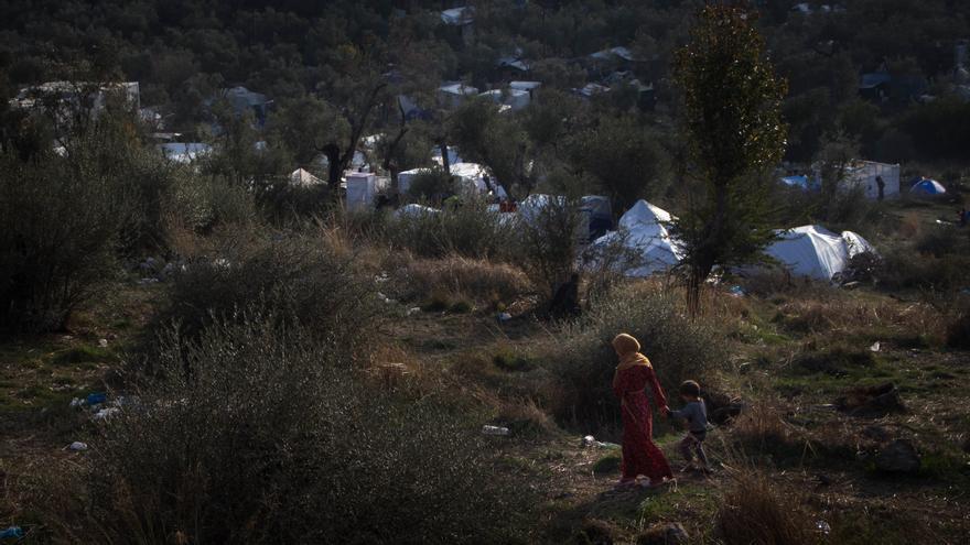 Una madre camina con su hijo en el campo de Moria