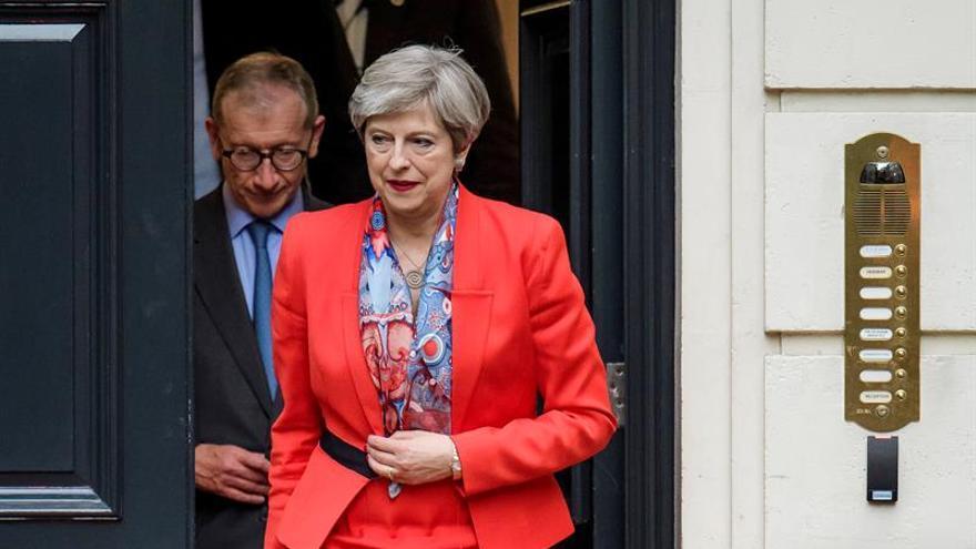May, con su marido detrás, dejan la sede del Partido Conservador en la mañana del viernes.