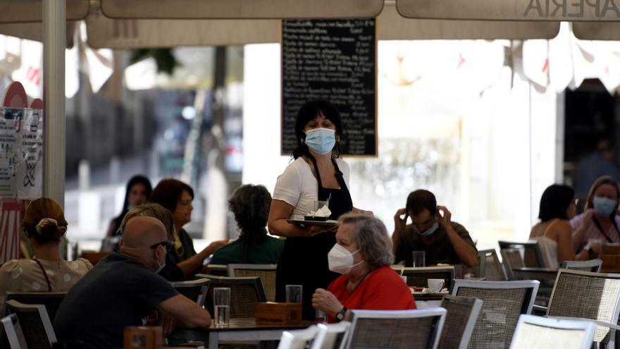 Una camarera con mascarilla atiende a los clientes en una terraza de un bar