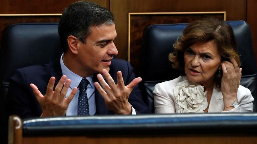 Pedro Sánchez conversa con Carmen Calvo durante el Pleno de investidura.