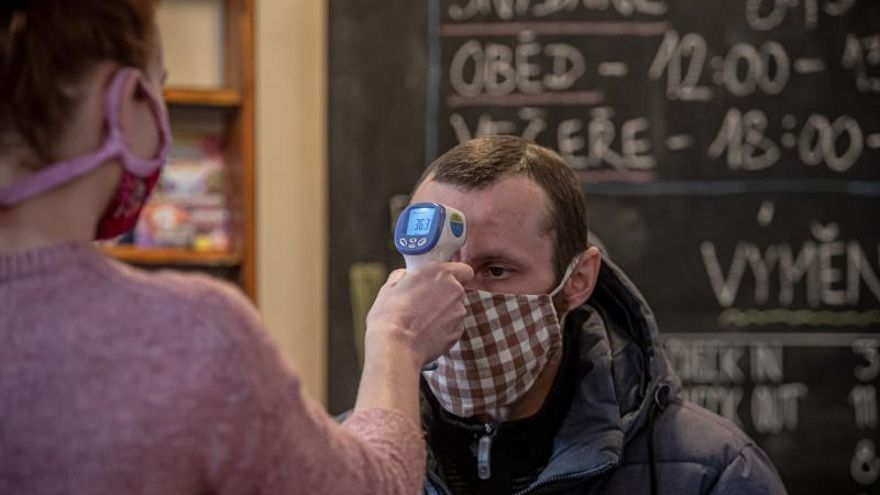 Una mujer le toma la temperatura a un hombre en la recepción de un albergue en Praga.