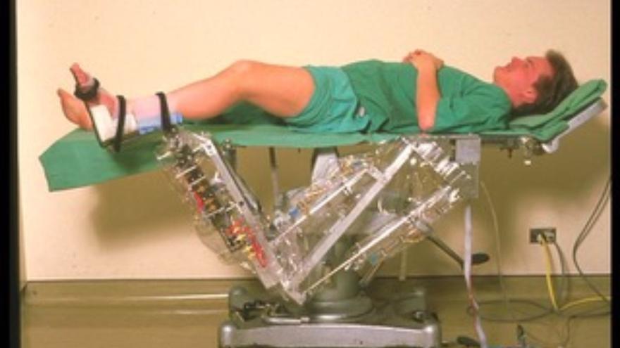 Primer prototipo de Arthrobot, a finales de 1984. Sobre la camilla hay un voluntario del equipo de ingenieros (Imagen: Cedida por Geof Auchinleck)