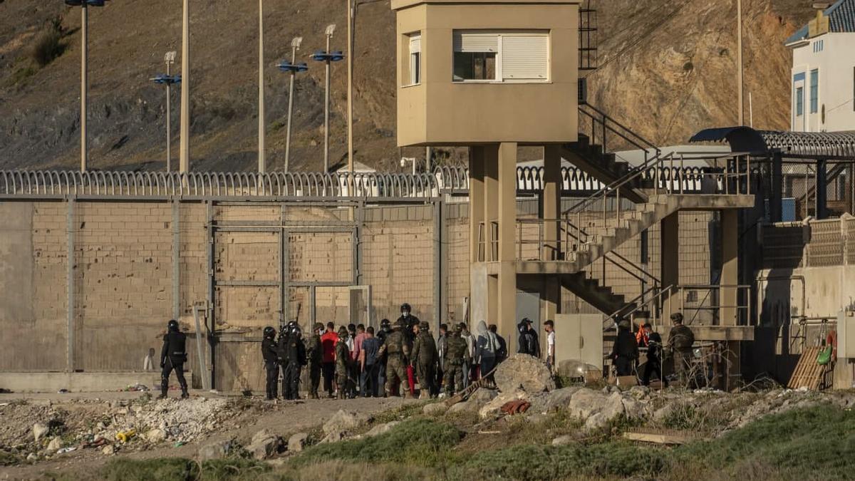 Varias personas son devueltas a través de la valla que separa España de Marruecos tras entrar en Ceuta. 19 de mayo de 2021.