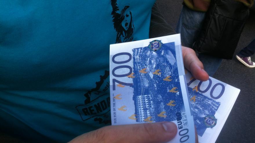 Durant la manifestació s'han repartit bitllets de 700 euros amb els que es representava un mes de renda bàsica / João França